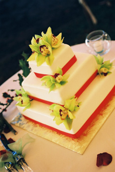Rolled fondanr wedding cake with red ribbon